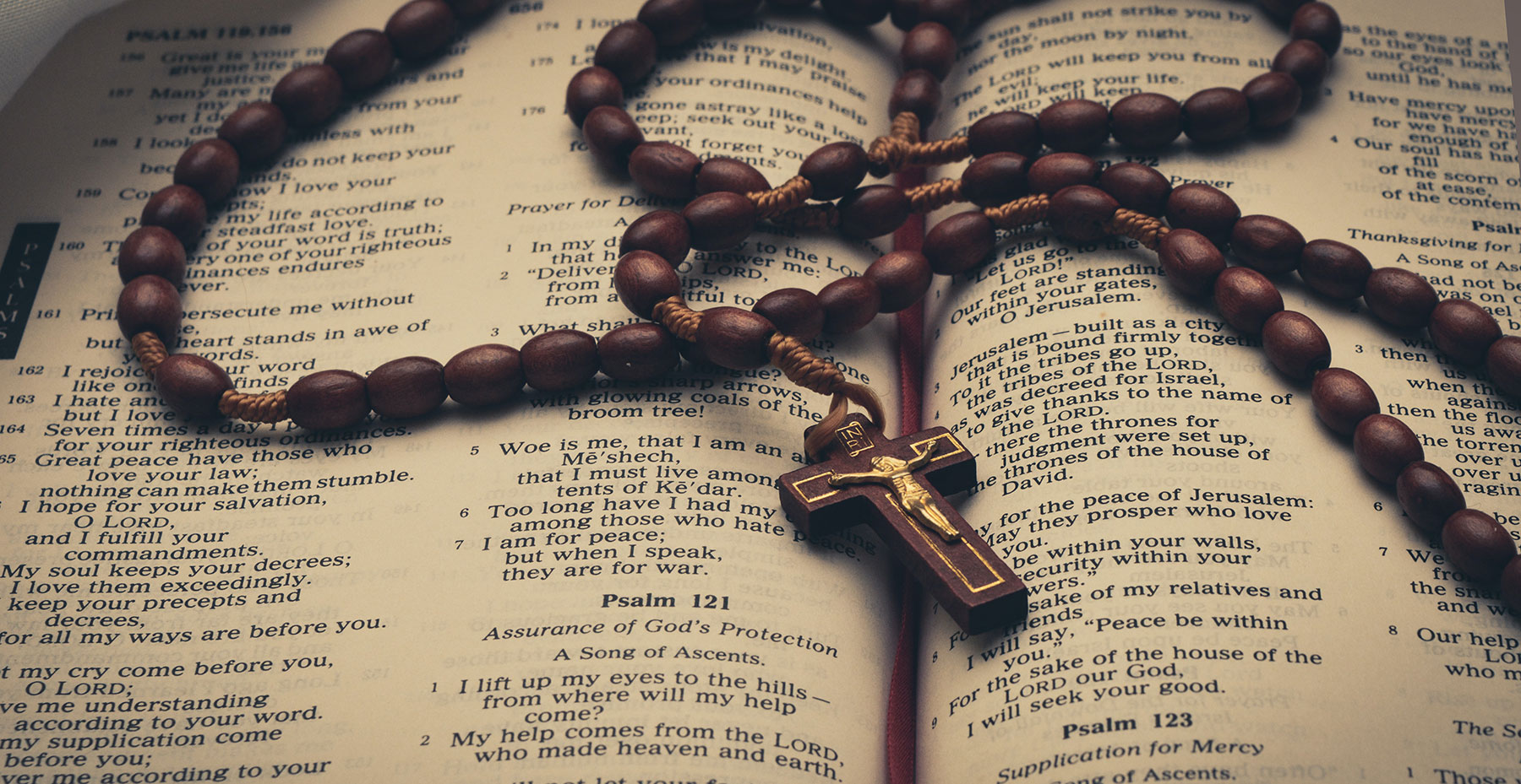 A rosary crucifix on a bible
